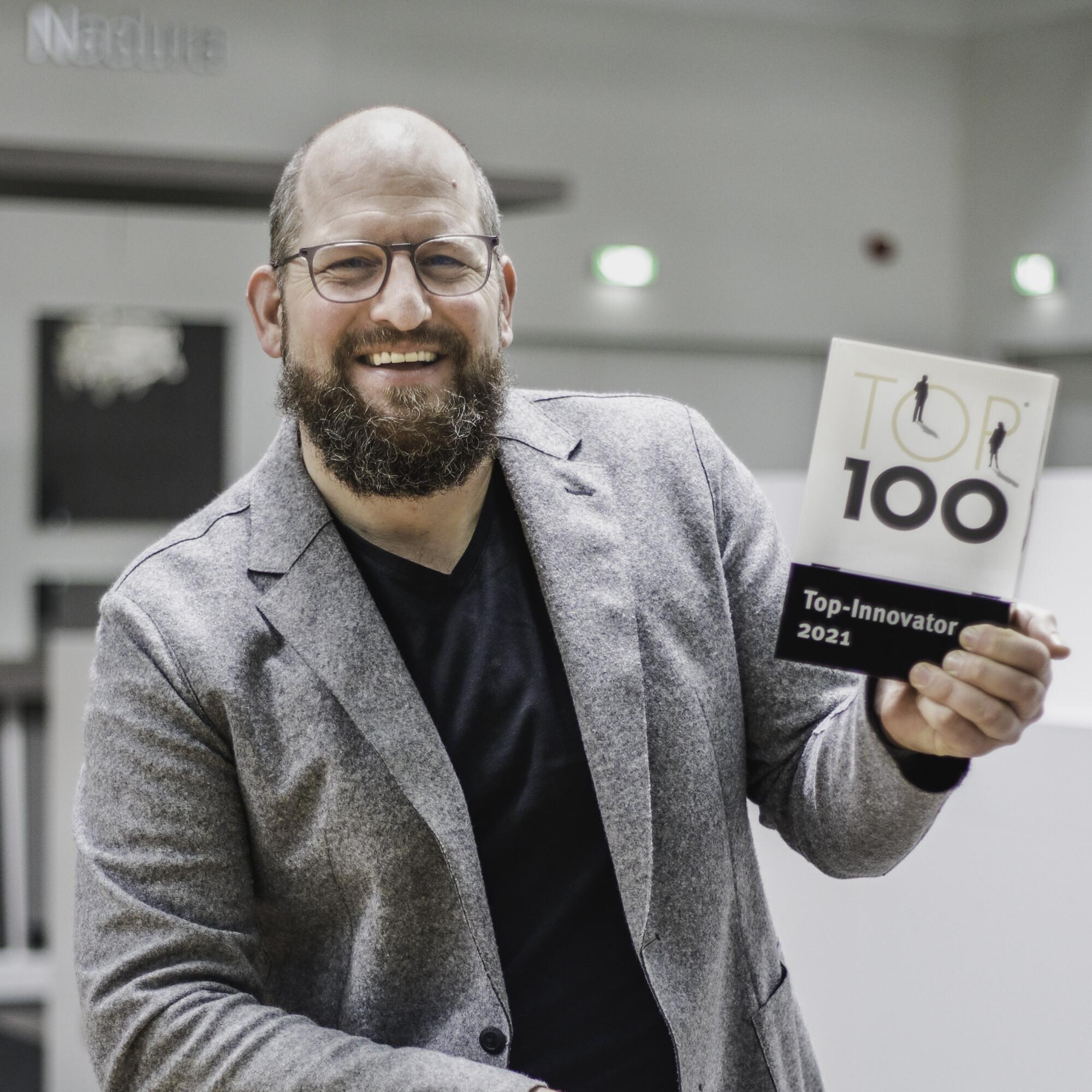 Geschäftsführer Guido Schulte präsentiert die TOP100 Auszeichnung